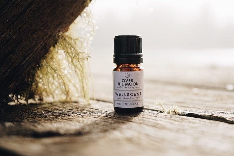 a small bottle of Over the Moon endocrine support essential oil on top of a wood.